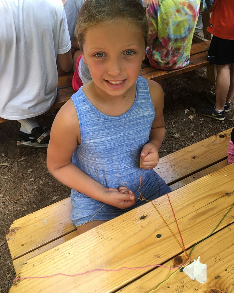 a camper smiles during the friendship bracelets activity