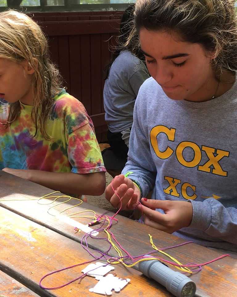 campers at picnic table making friendship bracelets