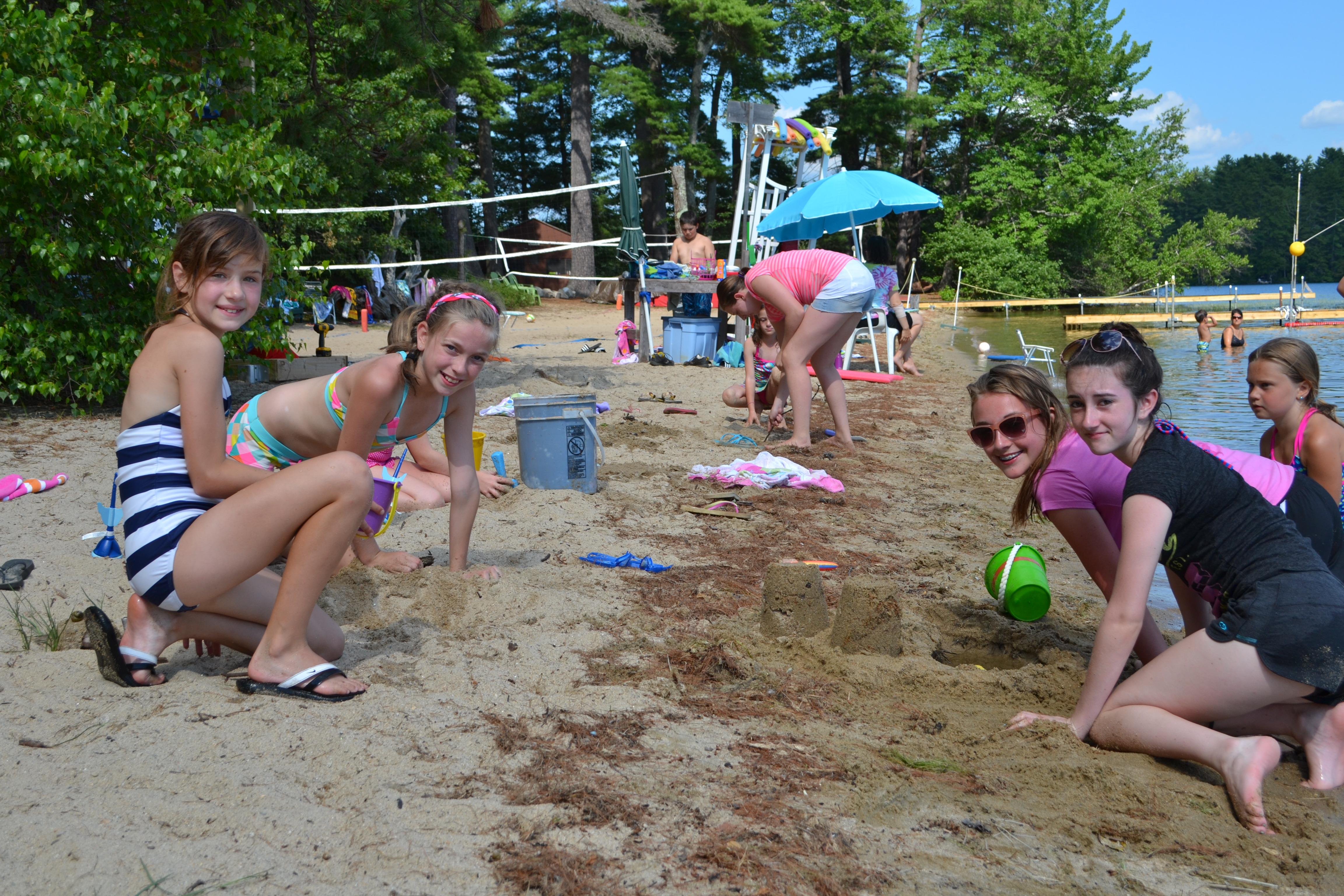Campers building sandcastles on the beach at the waterfront
