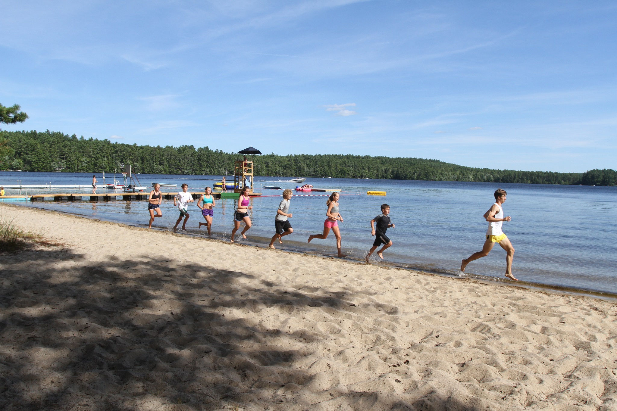 Campers running along the water on the beach