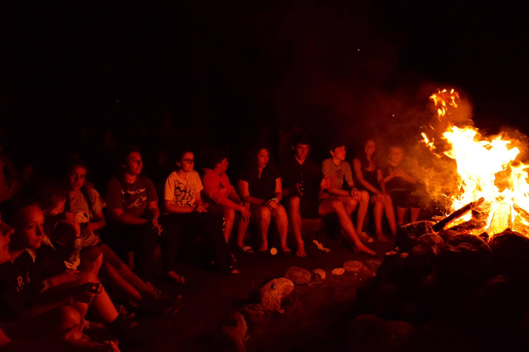 Campers singing around a roaring fire sitting on log benches