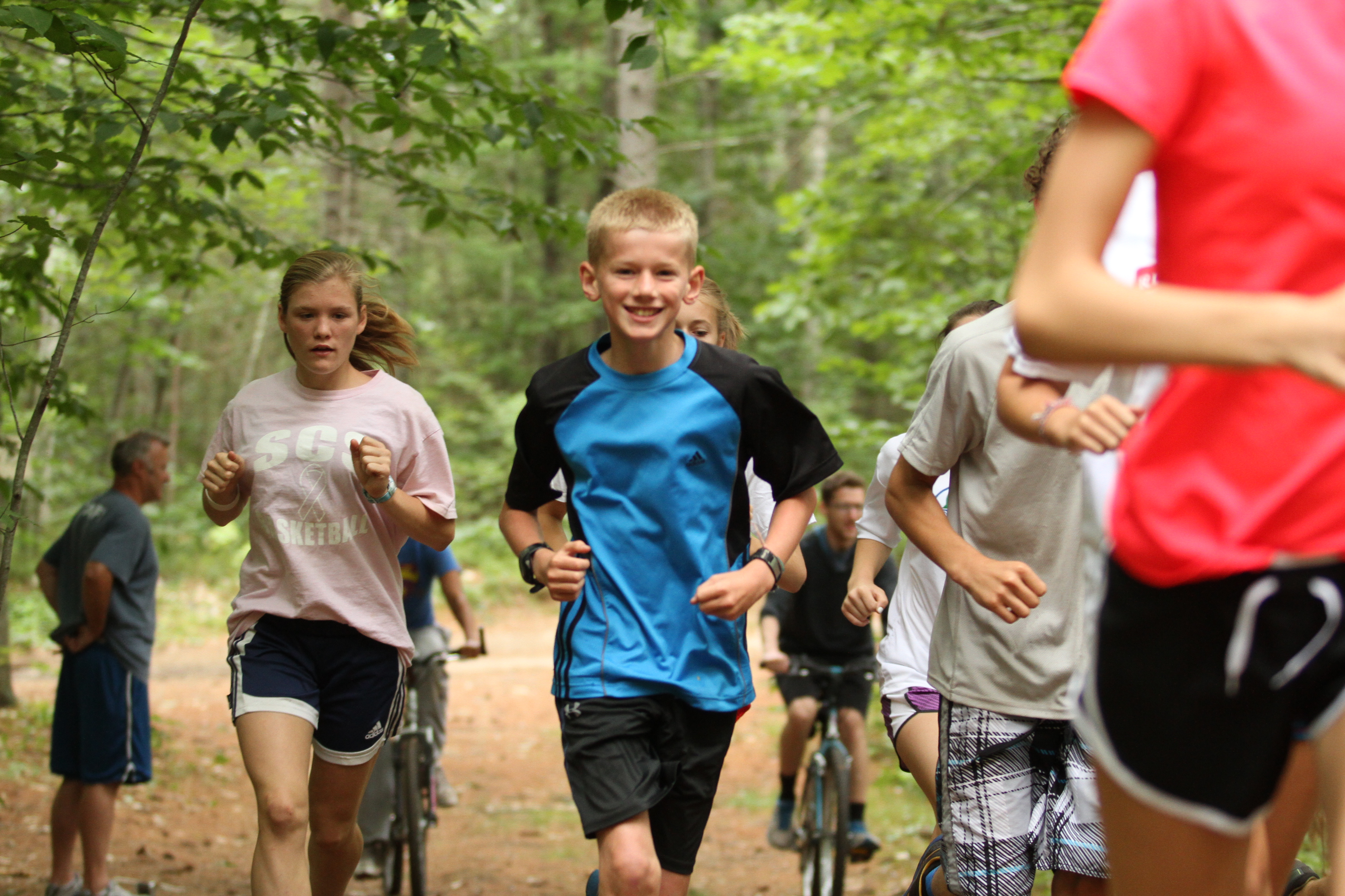 Campers running through a trail in the woods by a coach