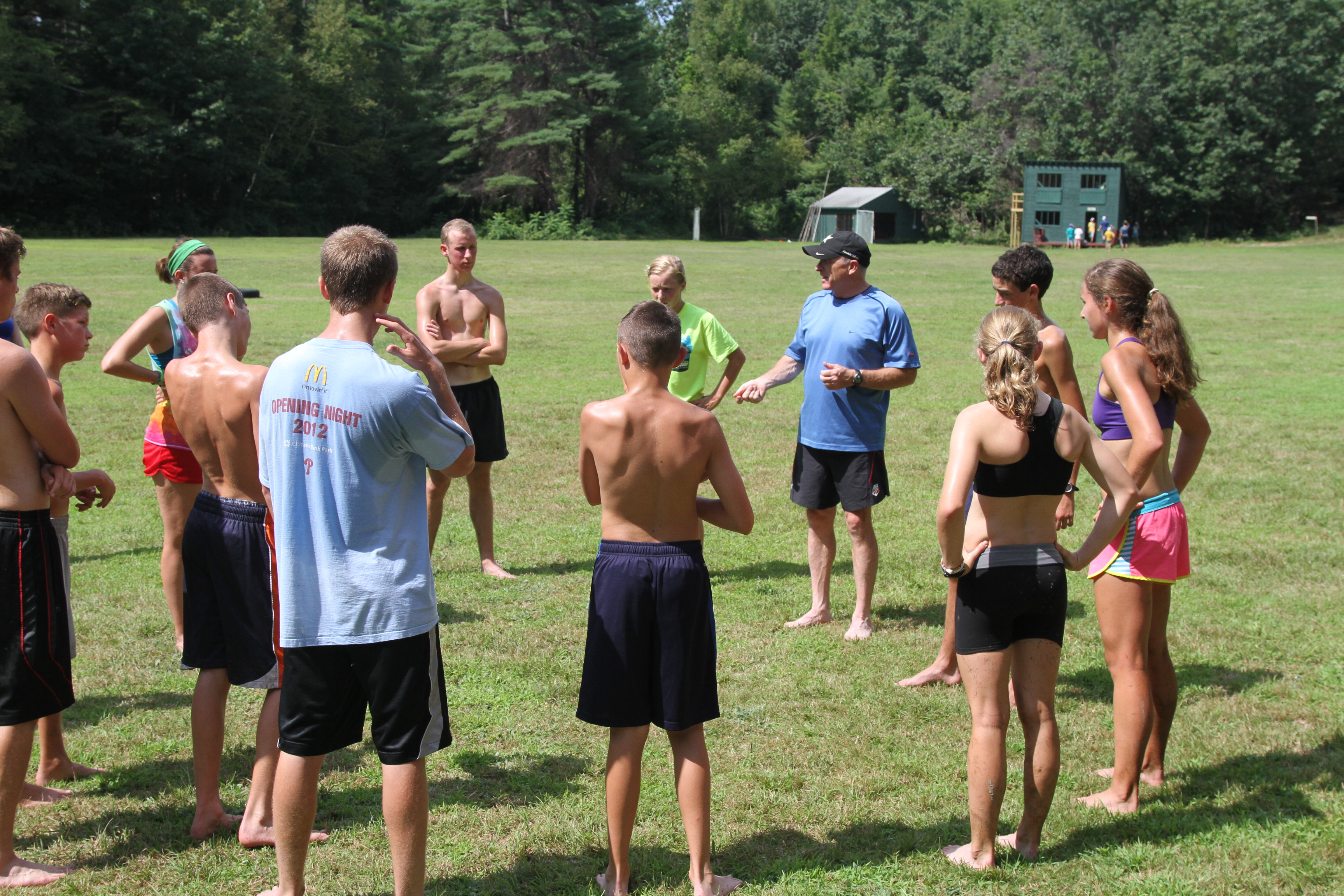 Campers receiving instruction in the field from a coach