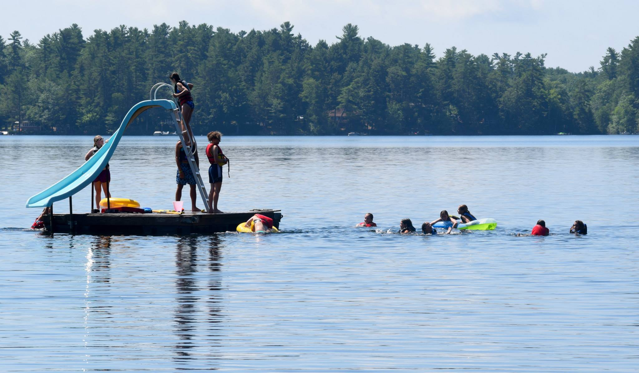 Campers swimming around a floating dock with a waterslide