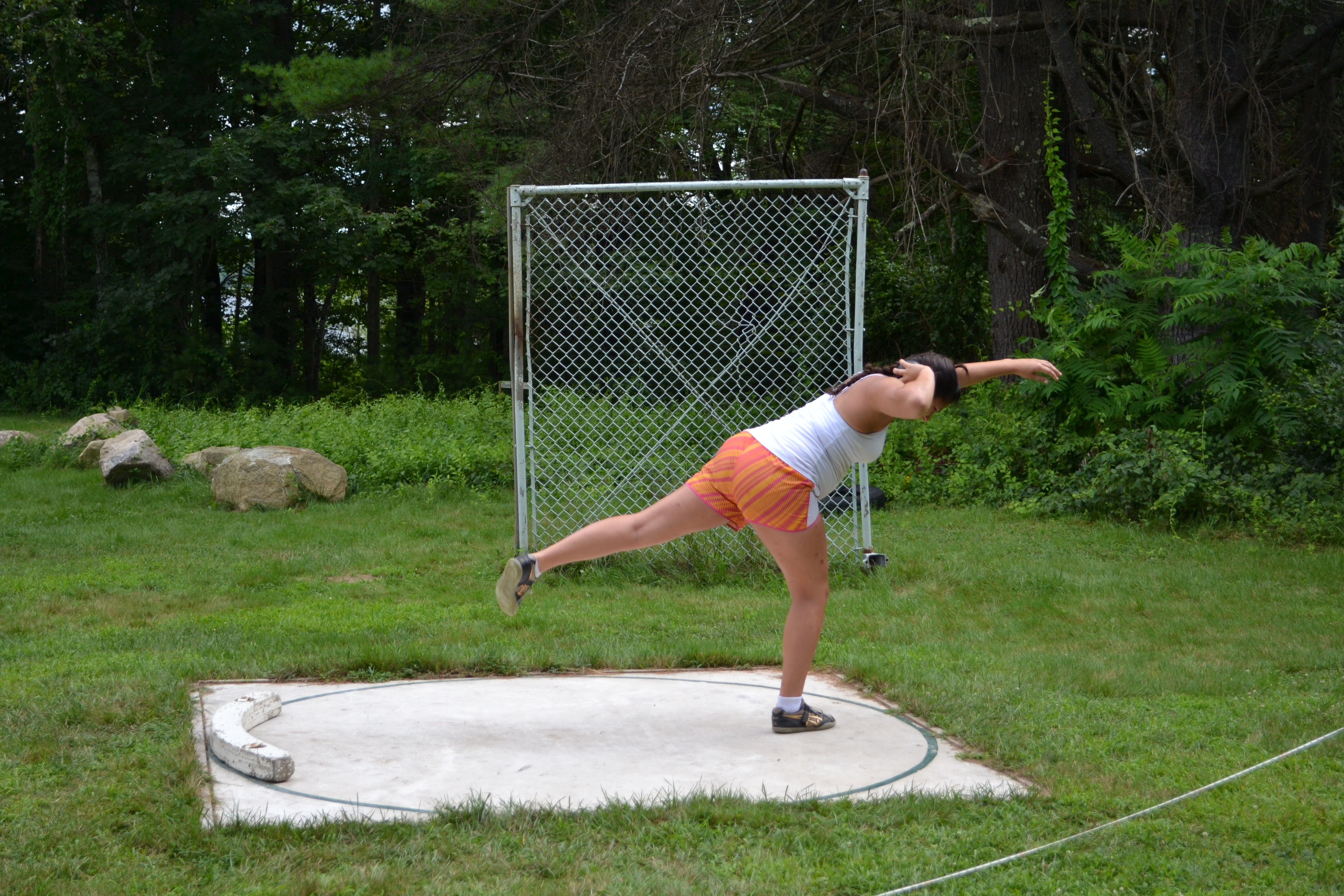 girl throwing the shot put by the woods