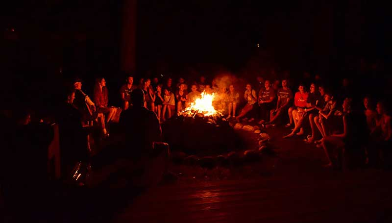 Campers sing around a campfire at slovenski camps