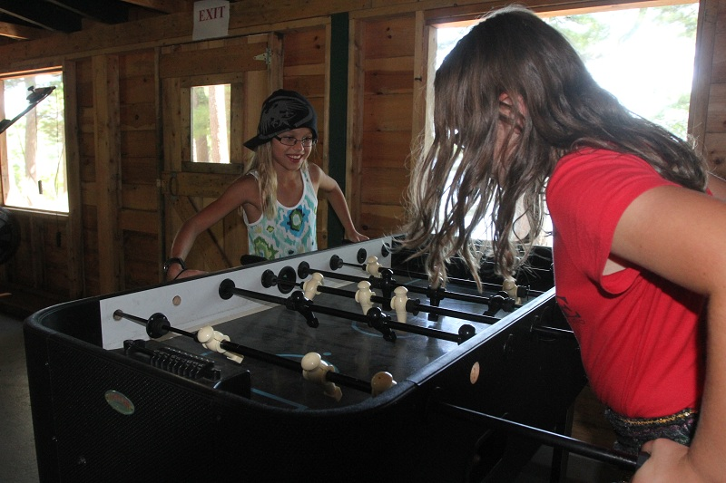 Campers playing foosball in the Maine Lodge